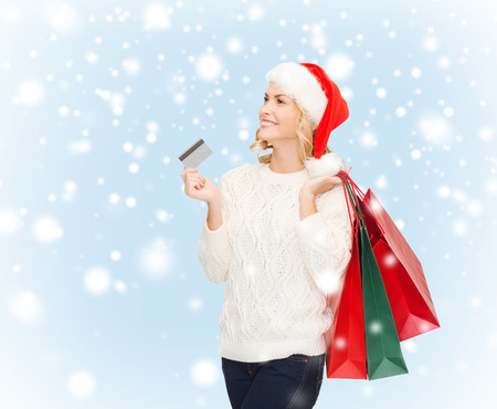 shopping, sale, gifts, christmas, x-mas concept - smiling woman in santa helper hat with shopping bags and credit card photo