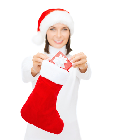 christmas, x-mas, winter and happiness concept - smiling woman in santa helper hat with small gift box and stocking photo