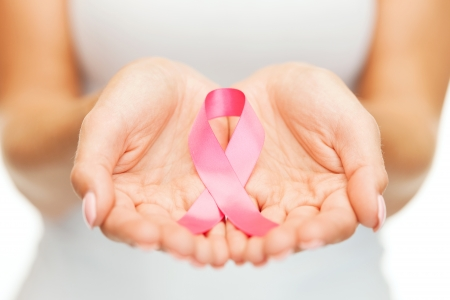 female breast: healthcare and medicine concept - womans hands holding pink breast cancer awareness ribbon