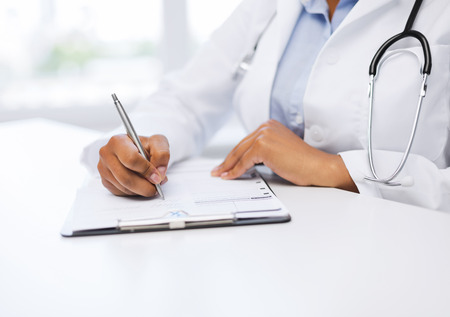 american staff: healthcare and medical concept - female doctor writing prescription Stock Photo