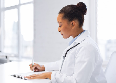 healthcare and medical concept - female doctor writing prescription Stock Photo - 24013692