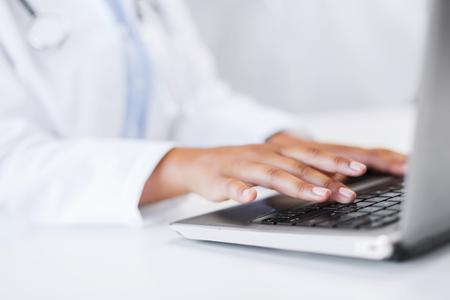 kantoor, gezondheid, geneeskunde, technologie en internet concept - vrouwelijke arts met haar laptop computer