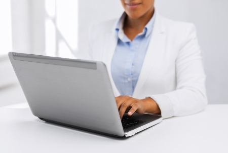 american media: office, business, technology and internet concept - businesswoman using her laptop computer