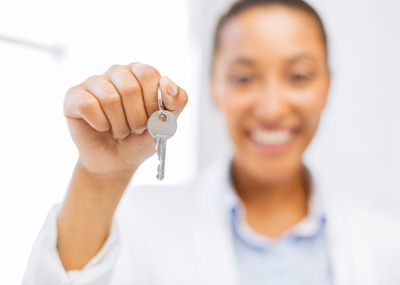 business, banking, real estate concept - woman hand holding house keys photo