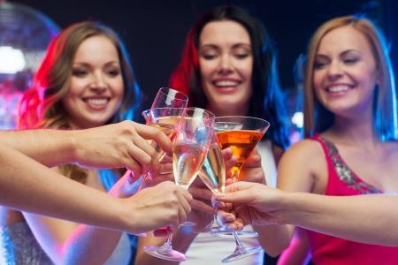 despedida de soltera: fiesta, celebración, amigos, bachelorette y el concepto de cumpleaños - tres hermosa mujer en vestidos de noche con cócteles y bola de discoteca