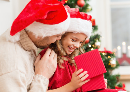 family, christmas, x-mas, winter, happiness and people concept - smiling father and daughter in santa helper hats opening gift box photo