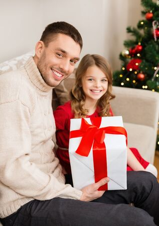 family, christmas, x-mas, winter, happiness and people concept - smiling father and daughter holding gift box Stock Photo - 24012997