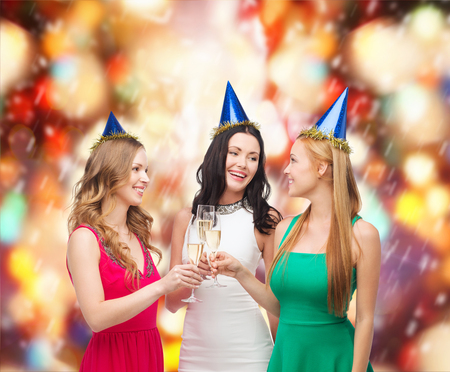 celebration, drinks, friends, bachelorette party, birthday concept - three smiling women wearing blue hats with champagne glasses photo