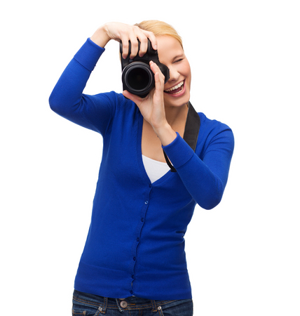 modern technology and people concept - smiling woman in casual clothes taking picture with digital camera photo