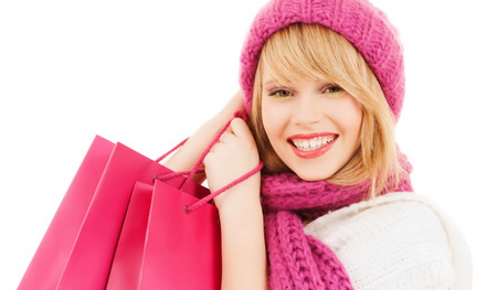 winter, people and happiness concept - woman in pink hat and scarf with many shopping bags photo