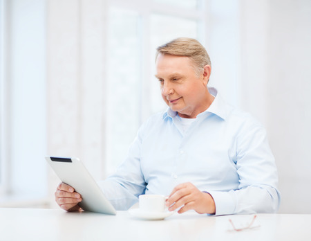 business, office, oldness, school and education concept - old man wearing eyeglasses with tablet pc computer at home photo