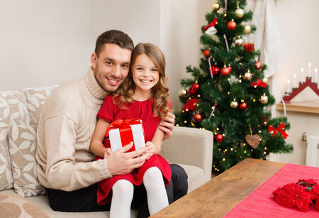christmas eve: family, christmas, x-mas, winter, happiness and people concept - smiling father and daughter holding gift box Stock Photo
