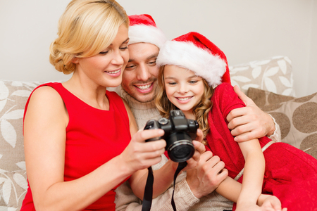 family, christmas, x-mas, winter, happiness and people concept - smiling family in santa helper hats looking at pictures photo