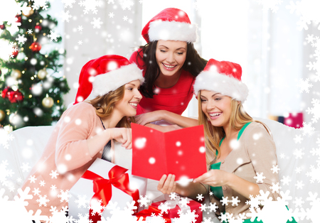 christmas, x-mas, winter, happiness concept - three smiling women in santa helper hats with card and many gift boxes photo