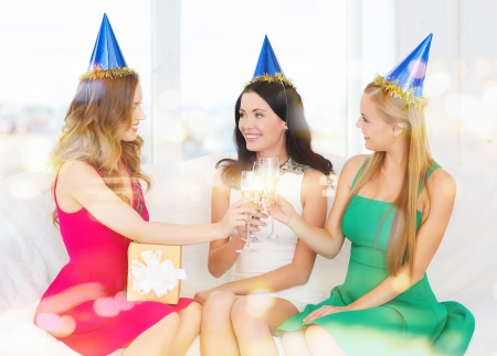 celebration, drinks, friends, bachelorette party, birthday concept - three smiling women wearing blue hats with champagne glasses and gift photo