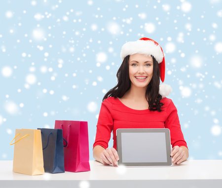 christmas, x-mas, electronics, gadget concept - smiling woman in santa helper hat with blank screen tablet pc Stock Photo - 24056851