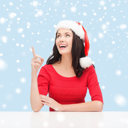 christmas, x-mas, winter, happiness concept - smiling woman in santa helper hat pointing to something Stock Photo - 24056854