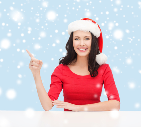 christmas, x-mas, winter, happiness concept - smiling woman in santa helper hat pointing to something Stock Photo - 24012631
