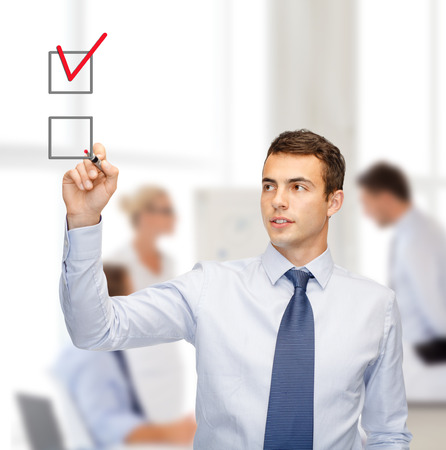 writing on glass: business and office concept - attractive buisnessman or teacher with marker drawning red checkmark into checkbox
