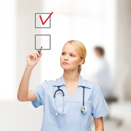 healthcare, medical and technology - young doctor or nurse with marker drawning red checkmark into checkbox photo