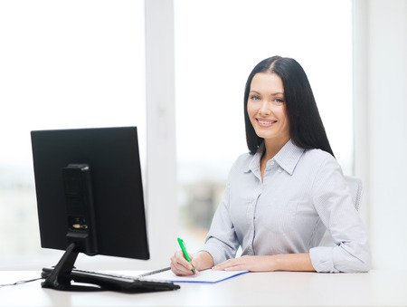 student studying: education, school, business and technology concept - smiling businesswoman or student studying Stock Photo