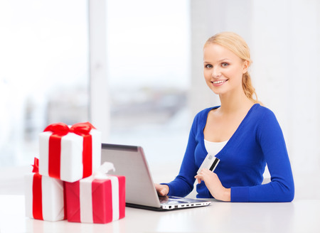 christmas, x-mas, online shopping concept - smiling woman with gift boxes, laptop computer and credit card photo
