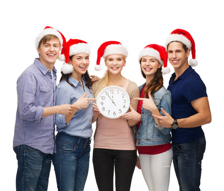 education, christmas, happiness and people concept - group of smiling students in santa helper hats with clock showing 12 photo