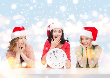 12 oclock: christmas, x-mas, winter, happiness concept - three smiling women in santa helper hats with clock showing 12