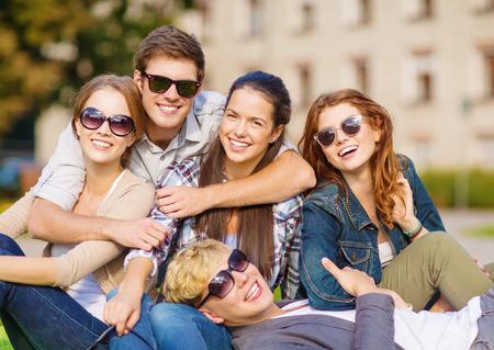 zomervakantie, onderwijs, campus en tiener concept - groep studenten of tieners opknoping uit Stockfoto