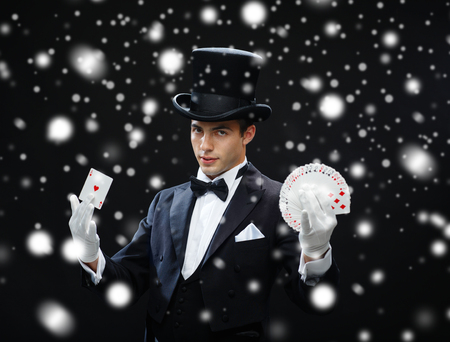 magic trick: magic, performance, circus, gambling, casino, poker, show concept - magician in top hat showing trick with playing cards Stock Photo