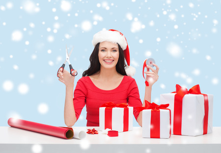 christmas, x-mas, winter, happiness concept - smiling woman in santa helper hat with many gift boxes photo