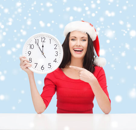 christmas, x-mas, winter, happiness concept - smiling woman in santa helper hat with clock showing 12 Stock Photo - 24070882
