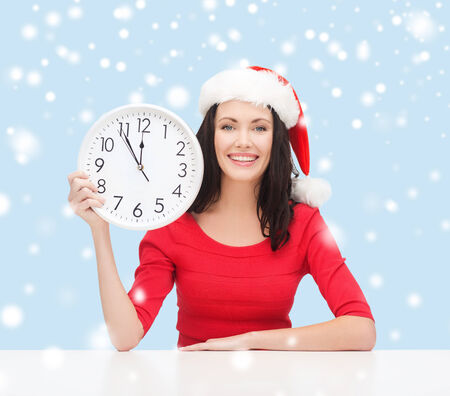 christmas, x-mas, winter, happiness concept - smiling woman in santa helper hat with clock showing 12 Stock Photo - 24070884