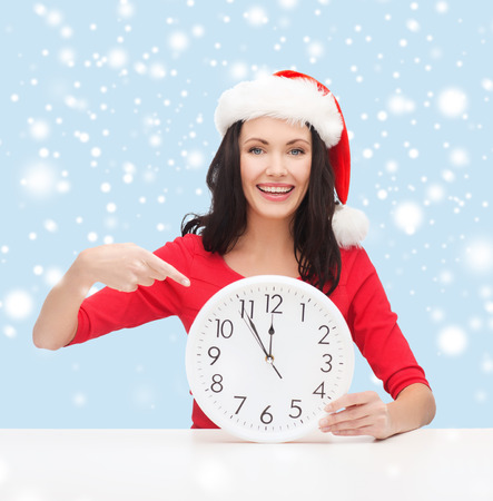 christmas, x-mas, winter, happiness concept - smiling woman in santa helper hat with clock showing 12 Stock Photo - 24070885