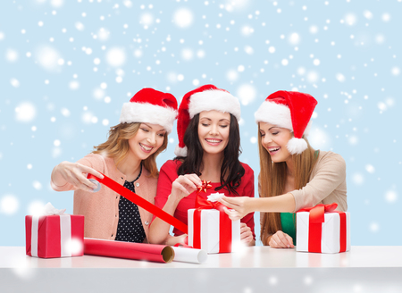 christmas, x-mas, winter, happiness concept - three smiling women in santa helper hats with gift boxes photo