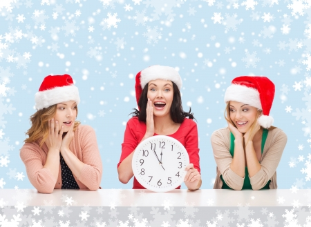 christmas, x-mas, winter, happiness concept - three smiling women in santa helper hats with clock showing 12 Stock Photo - 24070890