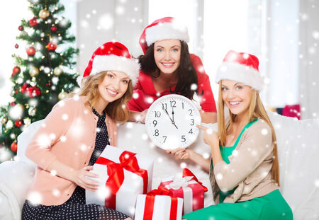christmas, x-mas, winter, happiness concept - three smiling women in santa helper hats with clock showing 12 and gift boxes Stock Photo - 24070896