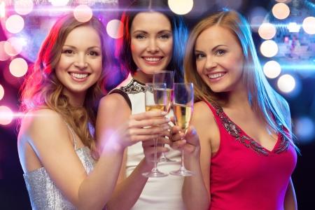 nieuw jaar, viering, vrienden, vrijgezellenfeest, verjaardag concept - drie mooie vrouw in avondjurken met champagneglazen