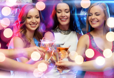vip beautiful: new year, celebration, friends, bachelorette party, birthday concept - three women in evening dresses with cocktails in club or bar