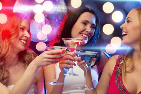 despedida de soltera: año nuevo, celebración, amigos, despedida de soltera, cumpleaños concepto - tres mujeres en vestidos de noche con cócteles y bola de discoteca