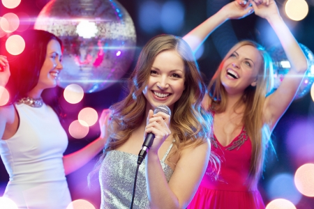 songs: party, new year, celebration, friends, bachelorette party, birthday concept - three women in evening dresses dancing and singing karaoke