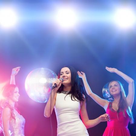 despedida de soltera: , año nuevo, celebración, amigos, despedida de soltera, el concepto de la fiesta de cumpleaños - tres mujeres en vestidos de noche bailando y cantando en el karaoke