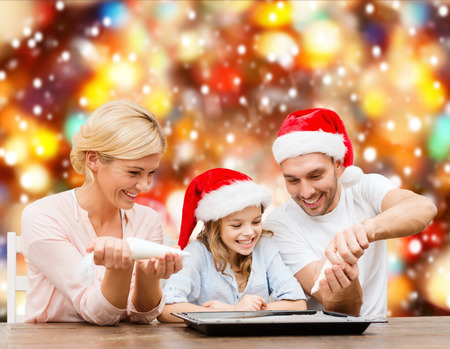 food, family, christmas, hapiness and people concept - smiling family in santa helper hats decorating cookies with glaze photo