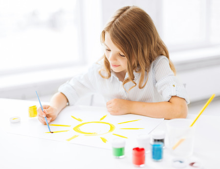creating: education, school, art and painitng concept - little student girl painting picture Stock Photo