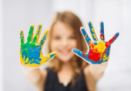 children painting: education, school, art and painitng concept - little student girl showing painted hands