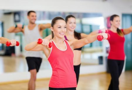 Fitness, Sport, Training, Fitness-und Lifestyle-Konzept - Gruppe von lächelnden Menschen arbeitet mit Hanteln im Fitness-Studio Standard-Bild - 24071539