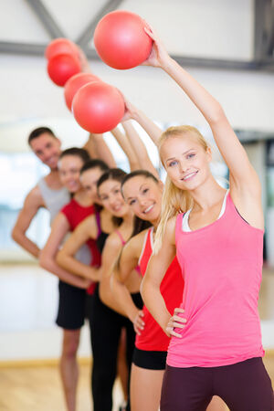fitness, sport, training, gym and lifestyle concept - group of smiling people working out with stability balls in the gym photo