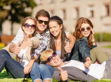 summer holidays, education, campus and teenage concept - group of students or teenagers showing thumbs up photo