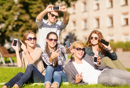 mobile telephones: education, technology, internet, summer holidays, social networking and teenage concept - group of teenagers with smartphones