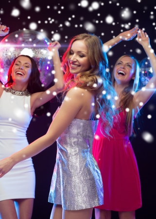 new year party: party, new year, celebration, friends, bachelorette party, birthday concept - three beautiful women in evening dresses dancing in the club